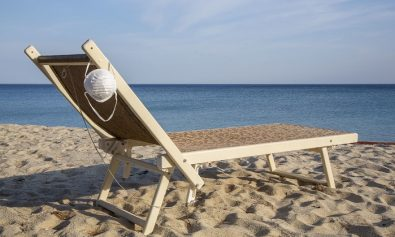 Protective mask on the beach chair. Desert beach due to Coronavirus (Covid19) quarantine. Campo nell'Elba, Italy